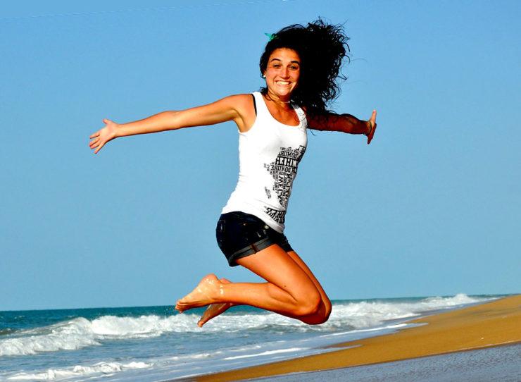 una ragazza salta sulla spiaggia